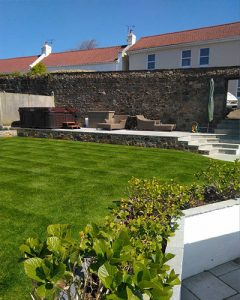 patio-landscaping company in Guernsey. Patio area with seating and hot tub.