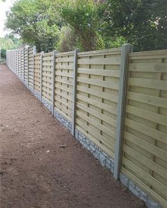 fence erector in Gurnsey photo of a wooden panel fence with concrete pillars and stone effect base.