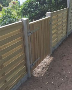 garden fencing Gurnsey photo of a wooden panel fence and gate with concrete pillars and stone effect base.
