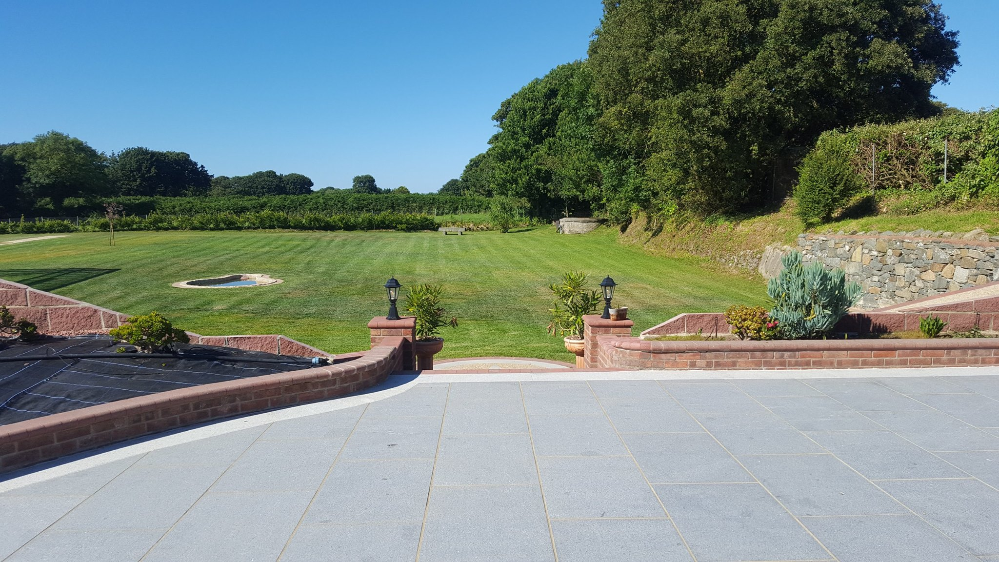 Guernsey landscaping services company. New landscape design and installation that consists of a large patio area with bespoke stone walls.