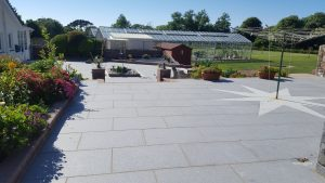 landscaping ideas for gardens in guernsey. Large modern grey patio area with steps leading down to a big garden and greenhouse