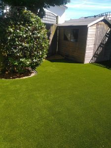 artificial grass installation for a customer in Guernsey. Bespoke fitting so grass neatly curves around garden hedges and shed.