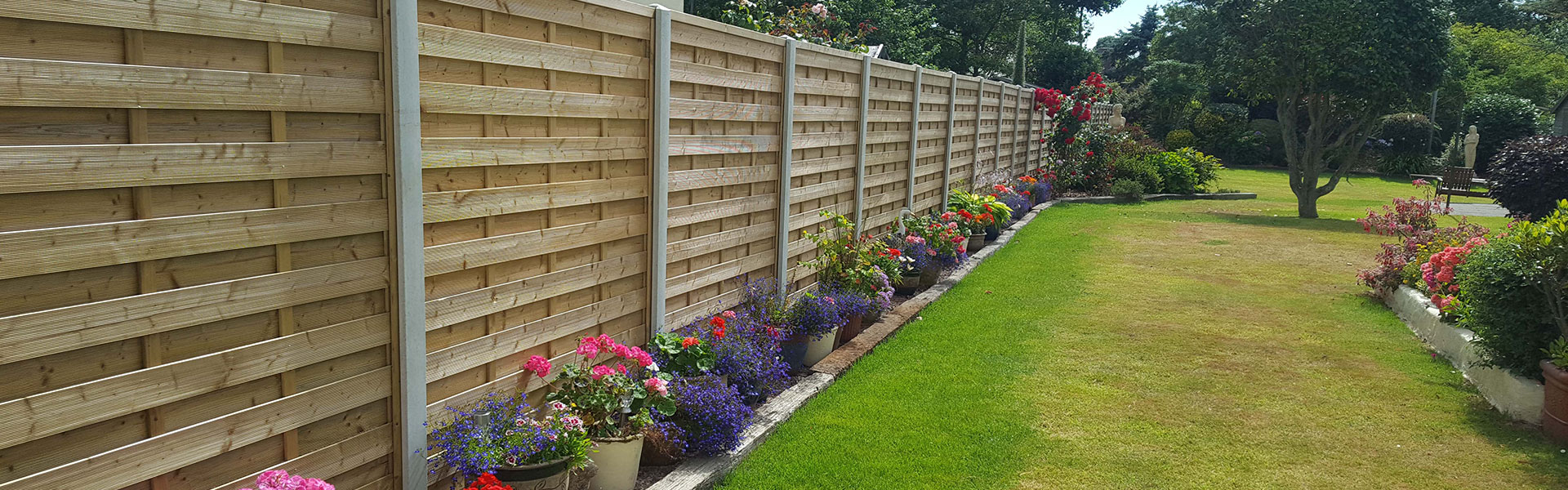 Guernsey garden fencing header photo of a beautiful wooden fence with concrete posts.