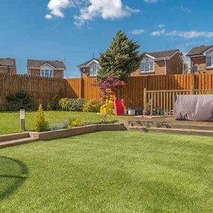 Artificial grass in Guernsey feature image showing a small garden on a sunny day.