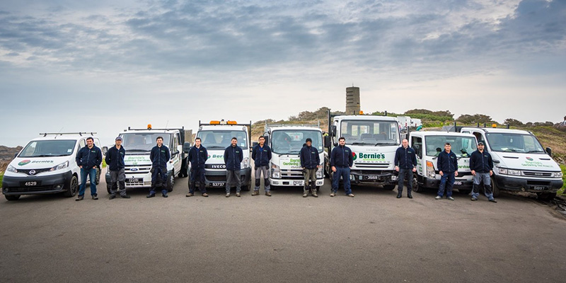 Bernie's Gardening Services team photo with the branded vehicles.