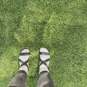 Overhead of woman wearing gray socks with black sandals and black jeans on faded artificial grass that was not UV protected.
