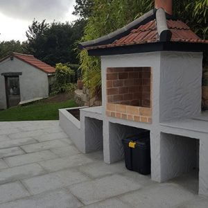 Custom mediterranean-style wood BBQ on a sunny day in Guernsey.