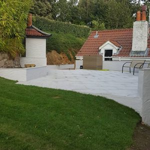 Grass side view of this finished landscaping project. This was our biggest project in 2019 as we used several tons of stone and concrete to create a custom seating area.