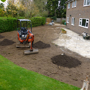 Digger in garden being used for garden landscaping.