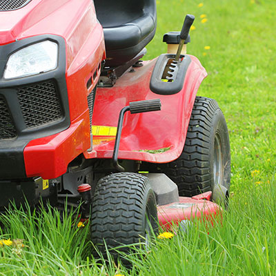 Red ride-on lawn mower cutting grass as part of our garden maintenance service.