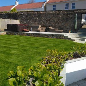 Garden services in Guernsey feature image shows landscaped garden with bespoke paving and stonemasonry flower bed.