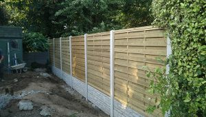 Quality garden fence with concrete posts and a stone effect boards at the bottom. Looks modern and clean.