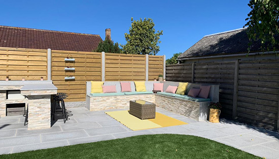 At Bernie's Gardening Services we provide a wide variety of garden services. Here you can see a newly landscaped modern garden with a bespoke seating bench, artificial grass and curved patio on a summers day.
