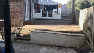 Before photo of old wooden decking before brand new patio.