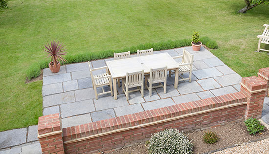 Large Guernsey back garden with lawn and stone patio with wooden patio furniture on a terrace in summer.