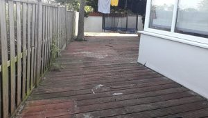 Before photo showing old rotten garden decking with a broken wooden fence.