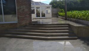 Grey Porcelain patio with steps and a new Griselinia hedge planted using rock-face concrete gravel boards has boundaries for a smart and lasting look.
