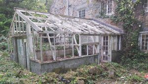 An old broken greenhouse in Guernsey attached to back of house.