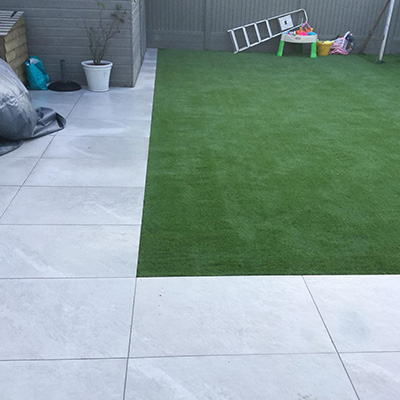 New porcelain patio installed in Guernsey garden with artificial grass.