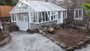 A fully restored greenhouse in guernsey with a brand new white metal roof and windows.